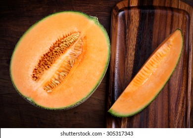 Organic cantaloupe with utensils on wooden table.
