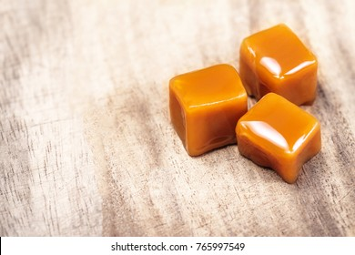 Organic caramel candies and caramel sauce on wooden background, Golden Butterscotch toffee, copyspace.