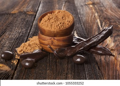 Organic carob bean,  pod and carob powder isolated on white background. Healthy cocoa alternative.