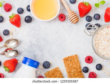 Organic cereal granola bar with berries with honey spoon and jar of oats and bottle of milk drink on stone background. Top view. Strawberry, raspberry and blueberry with almond nuts.
