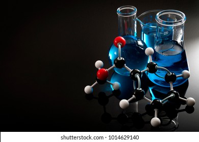 Organic chemistry, science class and STEM research concept with a methyl benzoate molecule on blue chemical solution in chemistry glassware, Erlenmeyer and Boiling (or Florence) flasks with copy space