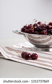 organic cherries in silver colander