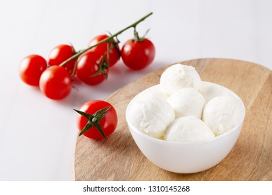 Organic cherry tomatoes and mozzarella in ceramic plate on white background. Top view. Lay Flat. soft focus.