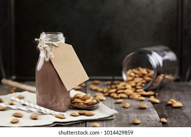 Organic chocolate almond milk with tag in a glass bottle with whole almonds spilled over a rustic wooden table.