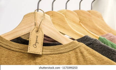 Organic clothes. Natural colored t-shirts hanging on wooden hangers in a row.