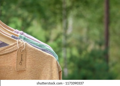 Organic clothes. Natural colored t-shirts hanging on wooden hangers in a row. Eco textile tag. Green forest, nature in background.
