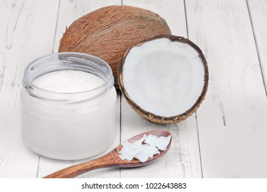 Organic coconut oil in a jar on wooden table