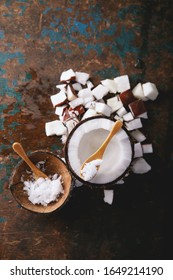 Organic coconut oil served with coconuts, shells and bits of coconut decorated with a sppon over a rustic wooden background. Top View