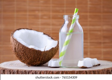 organic coconut water in a glass jar with tubule on natural background