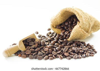 Organic coffee beans in sack and wooden coffee dipper on white background close up isolated.