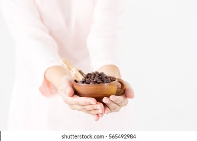 Organic coffee benas in vintage wooden cup on women's hand close up.