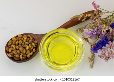 Organic cold pressed grapeseed oil in clear bowl with dried grape seeds in wooden spoon on marble background