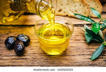 Organic cold pressed italian olive oil. Bottle pouring virgin olive oil in a bowl close up
