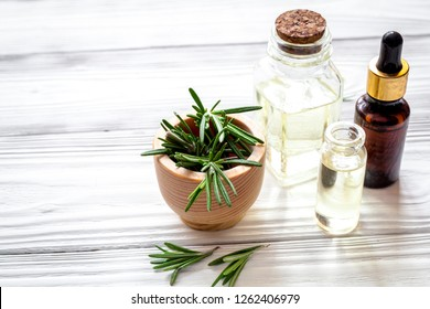 organic cosmetics with extracts of herbs rosemary on wooden back
