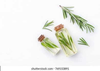 Organic cosmetics with extracts of herbs rosemary on white wooden background.