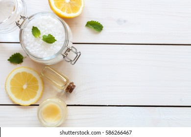 Organic cosmetics with lemon ingredients on white wood background, top view