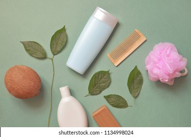 Organic cosmetics from natural ingredients. Coconut, shampoo, shower gel, pink sponge, tar soap, wooden comb and green leaves. Flat lay beauty photography bath products