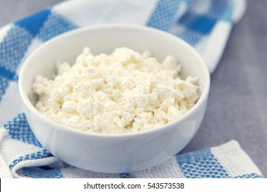 Organic cottage cheese in a white ceramic bowl on the kitchen table. Dairy products for the healthy breakfast. Healthy food concept