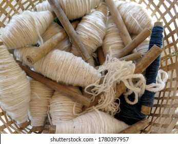 Organic cotton threads in the bamboo basket in rural village, Laos. Ethnic group of people is working traditional ways such as hand cotton spinning and weaving