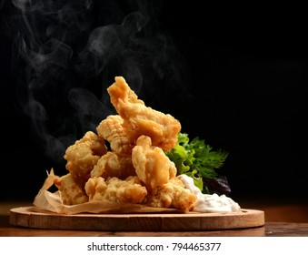 Organic Crispy fish Strips in batter on a black background