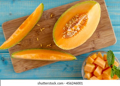 Organic cut cantaloupe melon slices siting on wooden cutting board with seeds and bowl of cut melon