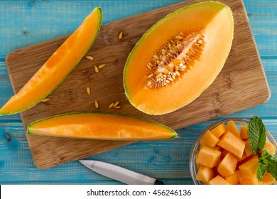 Organic cut cantaloupe melon slices siting on wooden cutting board with seeds and bowl of cut melon and knife