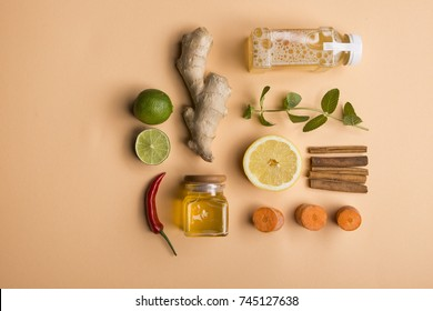 Organic detox juice with ginger, mint, lemon and lime ingredients on soft orange background. Tabl top view. Flat lay. Healthy frsh products