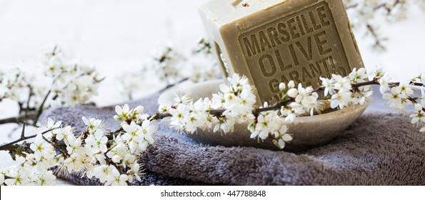 organic detox still-life - green Marseille soap with olive oil over towel and fresh white spring blossom flowers for body care beauty treatment