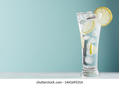 Organic detox water with yellow lemon slices, ice cubes, sparkling water in misted glass in modern mint color interior.