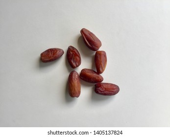 Organic Dried dates on a white background The characteristics of the dried leaves are dark brown and dry, attached to the stalks, sweet and natural.