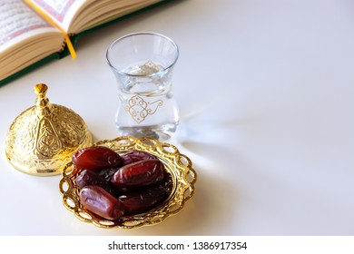 Organic dried dates in traditional arabic golden plate, cup of pure drinking water and quran book. Iftar Holy month Ramadan concept. Selective focus. Copy space.