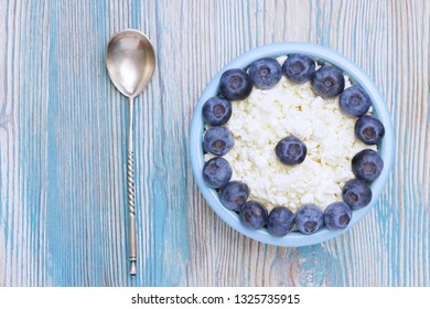 Organic eco healthy meal, dairy product.  An overhead photo of fresh natural cottage cheese with silver spoon and blueberries in a blue ceramic bowl on the wooden table. Top view with copyspase
