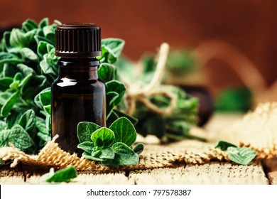 Organic essential oregano oil in a glass jar and a bunch of fresh marjoram, vintage wooden background, selective focus