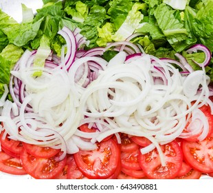 Organic, farm fresh, rinsed green lettuce, finely sliced onion rings and sliced red tomatoes primarily but not exclusively as toppings for American style hamburgers.