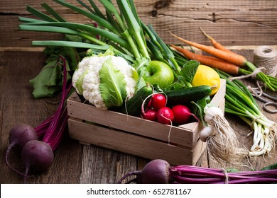Organic  farm. Fresh vegetables in crate,   cauliflower, garlic, radishes and cucumbers on rustic wooden background