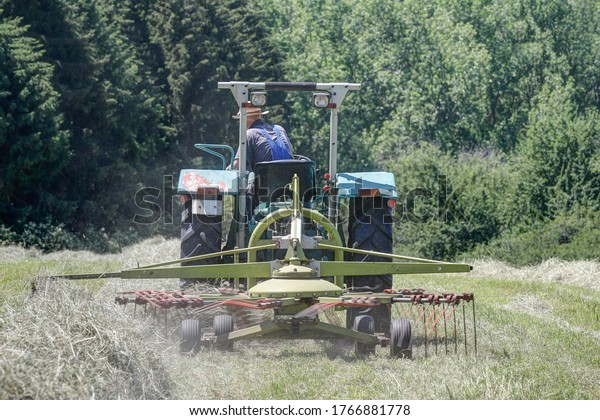 Organic farmer with his old tractor and rake, which processes the hay into a swath. The swath is required to further process the hay with the baler.