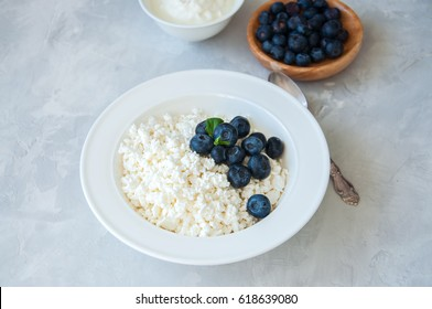 Organic Farming Cottage cheese in a plate sour cream and blueberries on a white stone background. Copy space.
