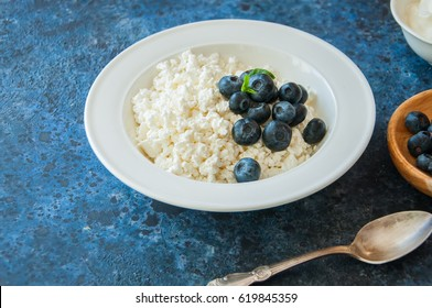 Organic Farming Cottage cheese in a white plate sour cream and blueberries on a blue stone background.