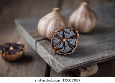 Organic Fermented Black Garlic on wooden table