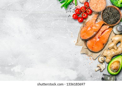 Organic food. Assortment of heathy food with raw salmon steaks . On a rustic background.