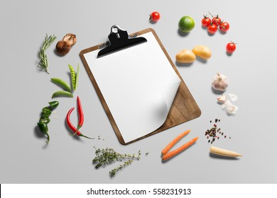 Organic food background. Food photography different vegetables and cliboard menu template on grey background. Copy space, isometric view
