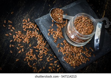 Organic food concept with flax seeds on dark wooden background