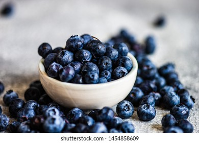 Organic food concept with ripe blueberry on rusty stone background