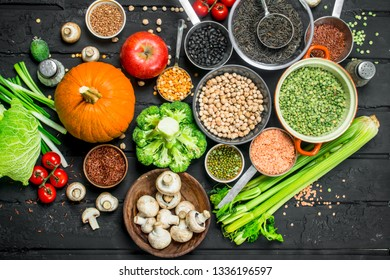 Organic food. Different range of fruits and vegetables with legumes. On a black rustic background.
