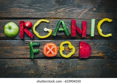 Organic food fresh vegetables flat lay lettering on dark wooden table top view. Nutrition meal ingredients concept. Nice cooking postcard, poster, banner.