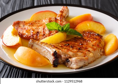 Organic food: grilled spicy pork with glazed fresh peaches and mint closeup on a plate. horizontal