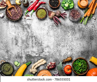 Organic food. Legumes with fresh vegetables. On a rustic background.