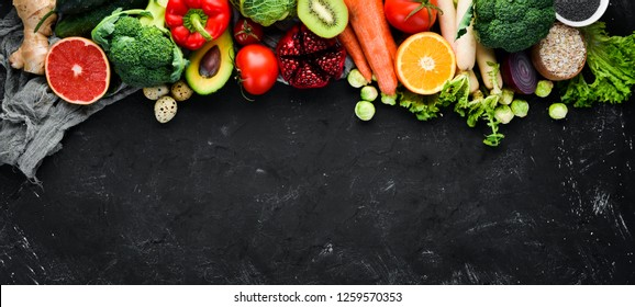 Organic food on a black stone background. Vegetables and fruits. Top view. Free copy space.