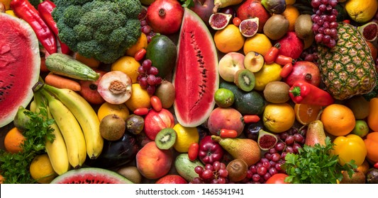Organic foods and fresh vegetables. Cucumber, Melon, pepper, Orangen lemon, carrot, broccoli, Ananas, Peaches, Kiwi, bananas, grapes and tomato on the table.