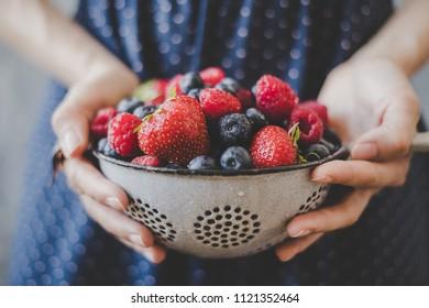 Organic fresh berries. Hands holding fresh juicy berries, closeup.